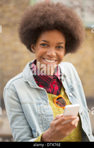 Woman using cell phone outdoors Banque D'Images