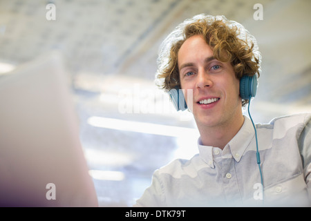 Woman listening to headphones in office Banque D'Images