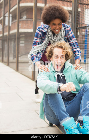 Couple playing on skateboard on city street Banque D'Images