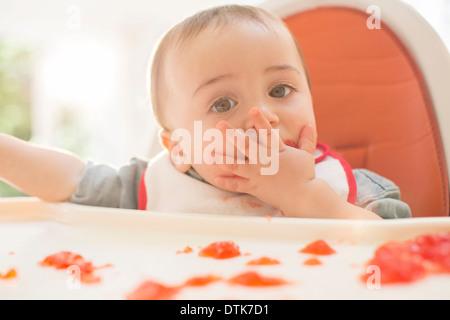 Baby Boy eating dessert la gélatine dans une chaise haute