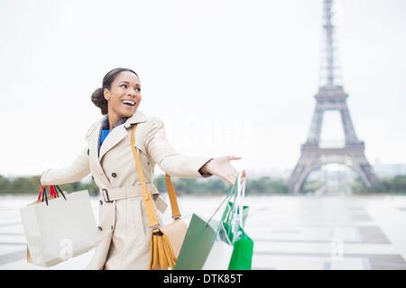 Woman carrying shopping bags par Eiffel Tower, Paris, France Banque D'Images