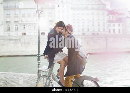 Couple hugging on à vélo le long de la rivière Seine, Paris, France Banque D'Images