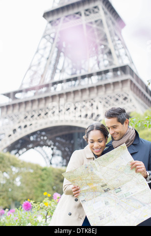 Couple reading map in front of Eiffel Tower, Paris, France Banque D'Images