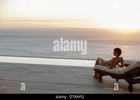 Woman in dress portant sur chaise de salon sur patio donnant sur l'océan au coucher du soleil Banque D'Images