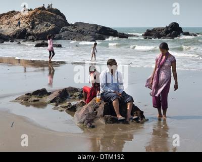 L'Inde, Goa, plage de Vagator, touristes indiens sittng sur des roches en mer Banque D'Images
