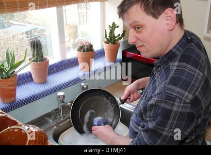 Man washing up pots/poêle avec peu d'enthousiasme à un évier de cuisine à la maison, England, UK Banque D'Images