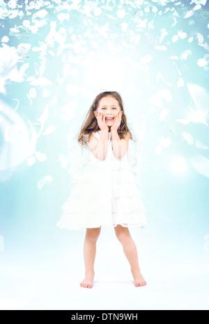 Cute little girl parmi les pétales de rose de vol Banque D'Images