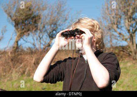 Blanc, blond teenage boy looking through binoculars lors d'une journée ensoleillée à la campagne anglaise birdspotting