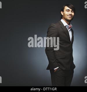 Young man wearing suit debout avec ses mains dans la poche à la recherche sur l'épaule. Beau male fashion model Banque D'Images
