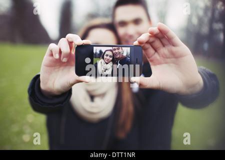 Mixed Race jeune garçon et fille faisant un drôle de visage tout en prenant un autoportrait avec téléphone mobile. Cute young couple.