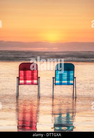 Les chaises de parterre en vagues sur la plage au coucher du soleil Banque D'Images