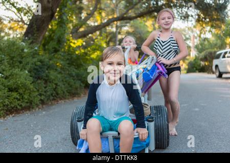 Les enfants en maillots poussant panier on rural road Banque D'Images