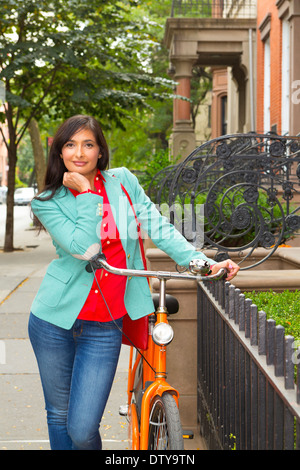 Mixed Race woman with bicycle, Brooklyn Heights, New York, United States