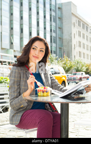 Mixed Race woman eating lunch at urban sidewalk cafe Banque D'Images