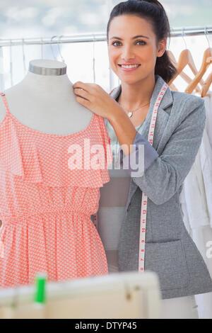 Smiling Fashion designer adjusting dress Banque D'Images