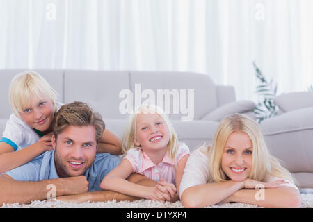Smiling family lying on the carpet Banque D'Images