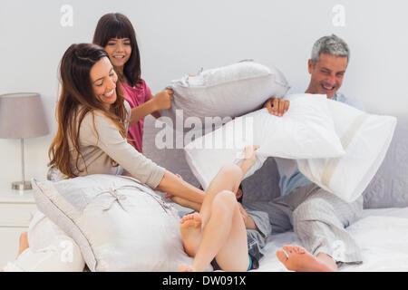 La lutte contre la famille ensemble avec des oreillers sur le lit Banque D'Images