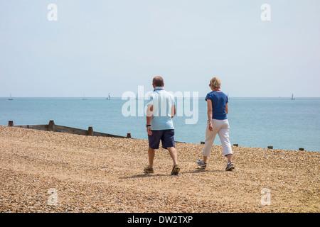 L'âge moyen en train de marcher sur une plage de Hayling Island, Hampshire Banque D'Images