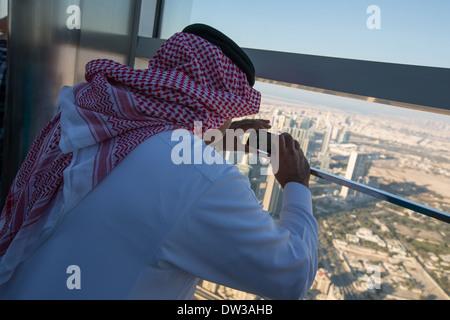Un homme d'Arabie prend une photo de la vue depuis le pont d'observation de Burj Khalifa, Dubai, Emirats Arabes Banque D'Images