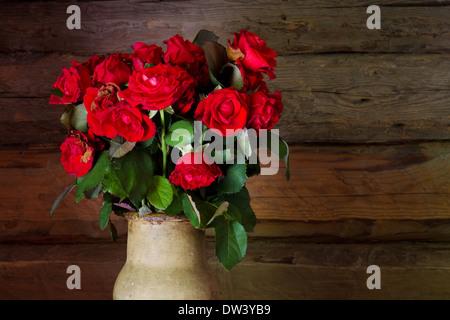 De belles roses avec des bourgeons et des feuilles flétries en ceramic jug sur fond baguette rustique en bois Banque D'Images