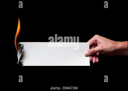 Woman's hand holding a burning paper - entrez propre légende. Banque D'Images