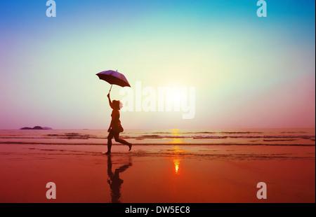 Happy woman jumping avec parasol sur la plage Banque D'Images
