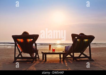Couple heureux admirer le coucher du soleil sur la plage Banque D'Images