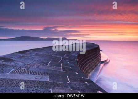 Le lever du soleil sur la côte jurassique au Cobb, Lyme Regis, dans le Dorset. L'hiver (février) 2013. Banque D'Images