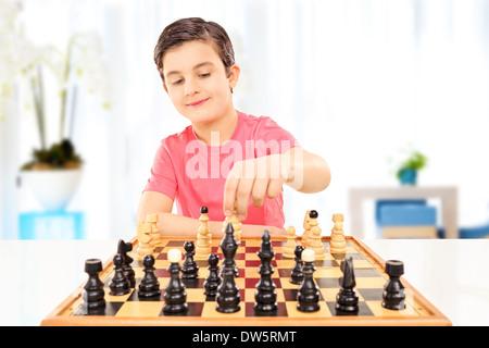 Petit Garçon jouant aux échecs assis sur une table à la maison Banque D'Images