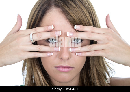Sad young woman peering through fingers Banque D'Images