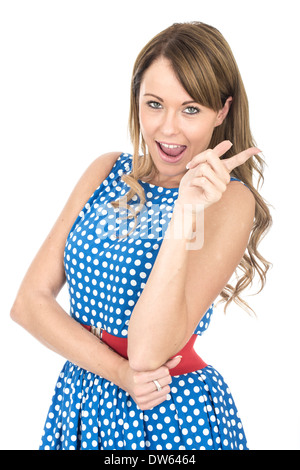 Young woman wearing blue polka dot dress pointing Banque D'Images
