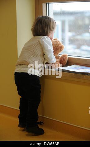 Fulda, Allemagne. Feb 18, 2014. Frieda regarde par une fenêtre avec un ours au cours d'une visite à l'hôpital de Banque D'Images