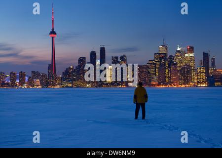 Homme marchant dans la neige au crépuscule sur le lac Ontario avec des lumières de Toronto city skyline en hiver