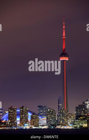 La tour CN de Toronto avec feux rouges et Skydome Rogers Centre la nuit en hiver Banque D'Images
