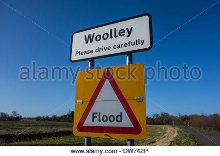 Panneau pour le village de Woolley dans Cambridgeshire ainsi qu'un signe d'inondation temporaire Banque D'Images
