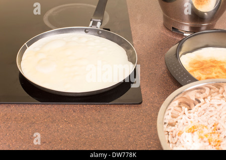 La friture de crêpes sur une plaque en céramique Banque D'Images