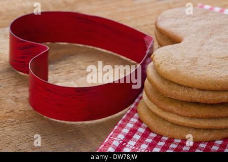 Emporte-pièce en forme de coeur rouge et un tas de pains de Noël maison brun sur fond de bois rustique Banque D'Images