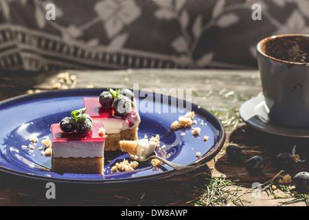 Dessert sur assiette en céramique bleue avec du café sur table en bois avec de l'herbe Banque D'Images