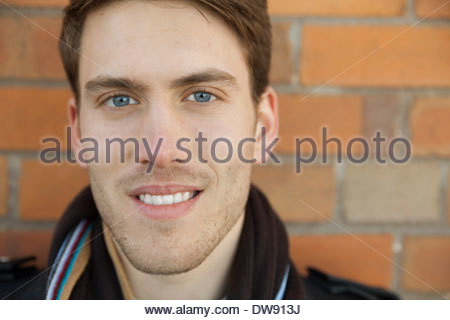 3f6290bd424e5a Close-up portrait of smiling man against brick wall Banque D Images