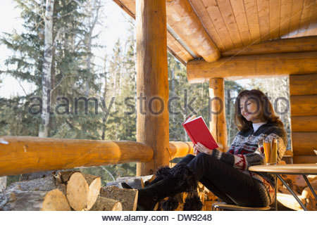 Senior woman reading book on cabin porch Banque D'Images