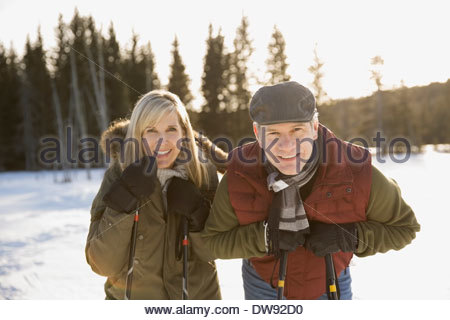 Portrait of smiling couple holding bâtons de ski en plein air Banque D'Images