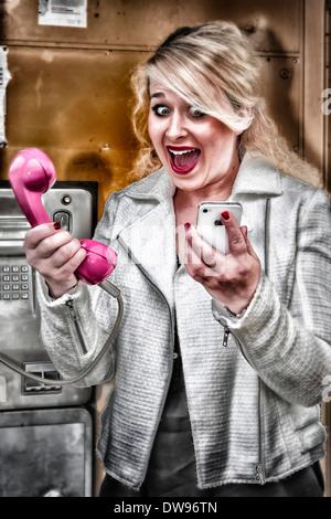 Jeune femme d'avoir à choisir entre un téléphone mobile et une cabine téléphonique Banque D'Images