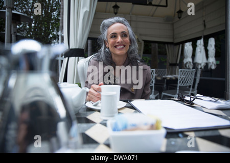 Young woman having coffee break sur porche de luxe