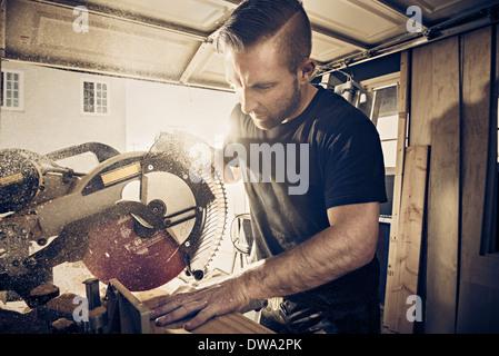 Male carpenter planche de bois de sciage en atelier Banque D'Images