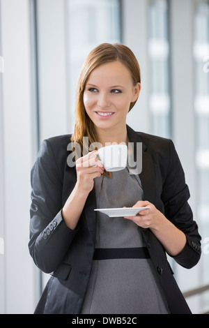 Beautiful businesswoman drinking coffee in office Banque D'Images