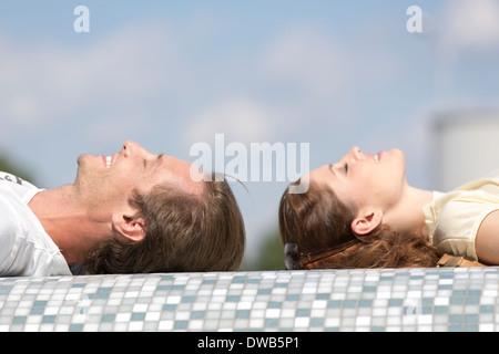 Vue latérale du couple relaxing on mosaic wall Banque D'Images
