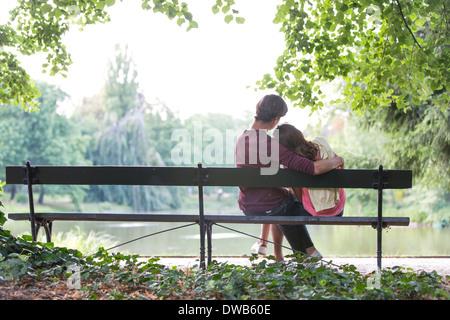 Vue arrière du romantic young couple sitting on bench at lakeside Banque D'Images