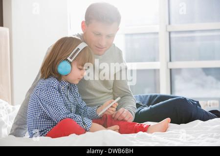 Père avec boy listening music sur le casque dans la chambre Banque D'Images
