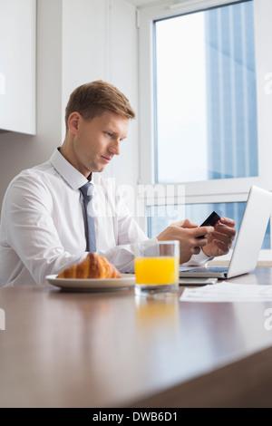 Mid adult woman with laptop on table de petit déjeuner Banque D'Images