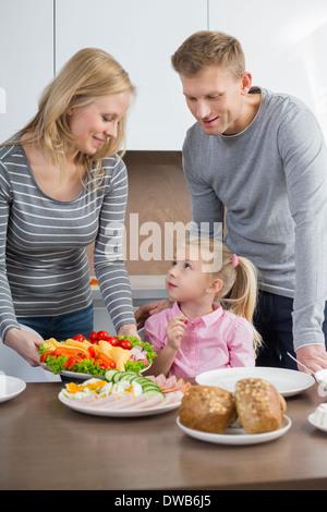 Heureux parents avec fille having meal in kitchen Banque D'Images